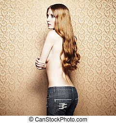 Fashion photo of the young sensual woman in jeans on a gold back