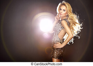 Fashion photo of young beautiful dancing woman with long flowing hair and shining dress.