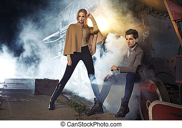 Fashion picture of two models next to the engine