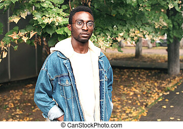 Fashion portrait african man wearing jeans jacket, eyeglasses in autumn park with leaves