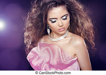 Fashion portrait. Beautiful woman with long curly hair and makeup over party lights. Elegant girl.