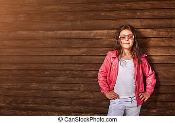 Cute little girl in pink jacket, sunglasses on wooden background