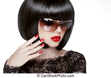 Fashion portrait of a beautiful brunette woman with shot hairstyle with red sunglasses. Red lips. Manicured nails.Isolated on white background. Studio photo