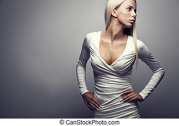 Fashion portrait of a blonde woman in white dress