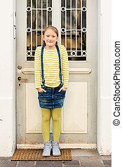 Fashion portrait of a cute little girl in a city