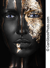 fashion portrait of a dark-skinned girl with gold make-up. ...