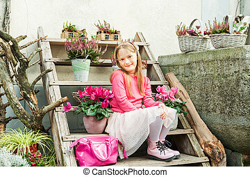 Fashion portrait of adorable little girl on a street in a city