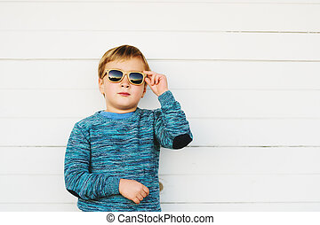 Fashion portrait of adorable toddler boy wearing blue knitted pullover and sunglasses
