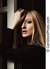 Fashion portrait of attractive blonde woman in a black dress posing in the shadow
