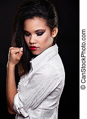 fashion portrait of beautiful american black female brunette girl model with bright makeup red lips in white shirt. Clean skin. Black background