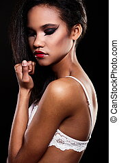 fashion portrait of beautiful american black female brunette girl model with bright makeup red lips in white lingerie. Clean skin. Black background