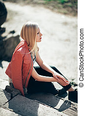 Fashion portrait of beautiful blond woman sitting on old stairs in sunlight