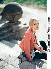 Fashion portrait of beautiful blond woman sitting on old stairs