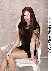 Fashion portrait of beautiful brunette woman in black dress sitting on moder chair
