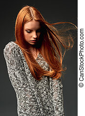Fashion portrait of beautiful red haired girl with flying hair