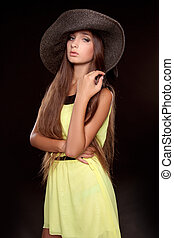 Fashion portrait of beautiful woman posing in hat isolated on black background