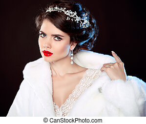 Fashion portrait of beautiful young woman in white fur coat with expensive jewelry, makeup and wedding hairstyle isolated on black background.