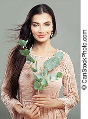 Fashion portrait of cheerful woman with green leaves