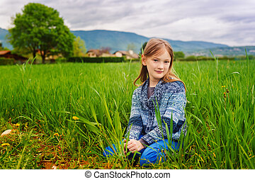 Fashion portrait of cute little girl of 7 years old, wearing blue trousers and knitted jacket
