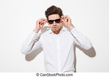 Fashion portrait of fancy man model dressed in shirt touching sunglasses and looking on camera with serious gaze, over white background with shadow