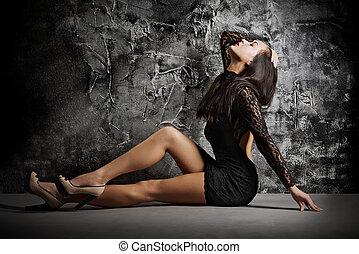 Fashion portrait of girl on grey wall