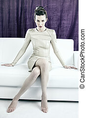 Fashion portrait of model with amazing crazy makeup and hair do science fiction sitting on couch