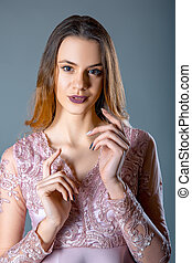 Fashion portrait of model woman on a blue grey background in lacy pink dress