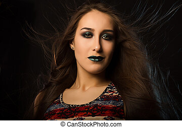 Fashion portrait of seductive tanned lady with flying hair and art makeup