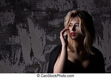 Fashion portrait of stylish blonde model with perfect skin posing at studio with shadows. Empty space