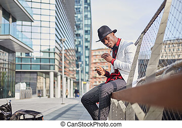 Fashion portrait of stylish young african man smoking cigarette