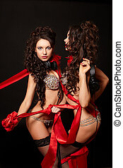 fashion portrait of two sexy brunette girls in light lingerie with long curly hair and jewellery bright makeup red lips with red ribbon isolated on black with headphones