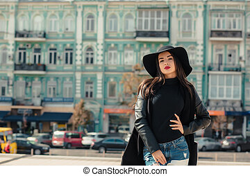 Fashion portrait of young attractive model wears wide-brimmed hat. Lady posing on a background of city
