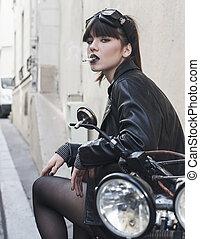 Fashion portrait of young beautiful teen biker girl posing outdoor.
