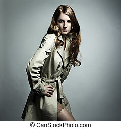 Fashion portrait of young beautiful woman in the raincoat