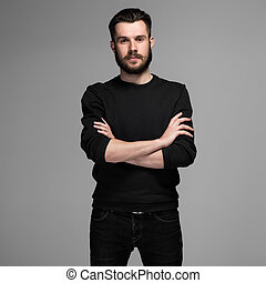 Fashion portrait of young man in black poses over gray...