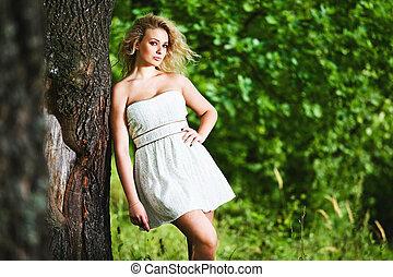 Fashion portrait of young sensual woman in garden.