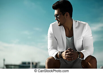Fashion portrait of young sexy businessman handsome model man in casual cloth suit in sunglasses sitting in the street behind blue sky