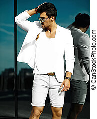 Fashion portrait of young sexy handsome model man in casual white suit in sunglasses in white suit in the street
