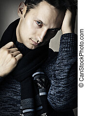 Fashion portrait of young stylish sexy man (male model) in dark blue shirt and black scarf