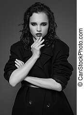 Fashion portrait of young woman in black coat