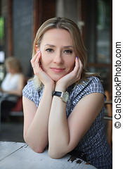 Fashion portrait of young woman sitting in a street cafe.