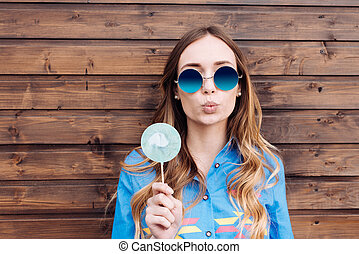 Fashion portrait pretty sweet young woman having fun with lollipop over wooden background