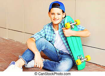 Fashion portrait smiling teenager boy with a skateboard on the street