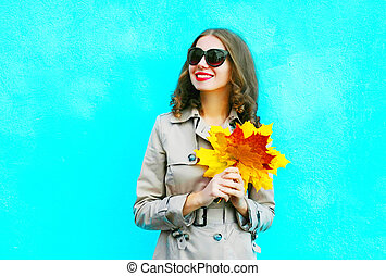 Fashion portrait smiling woman with autumn yellow maple leaves on a blue background