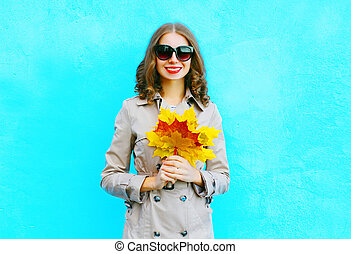 Fashion portrait smiling woman with autumn yellow maple leaves wearing a coat on a blue background