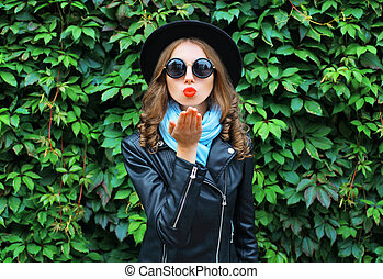 Fashion portrait young woman sends air kiss blowing red lips wearing a black hat over green leaves background