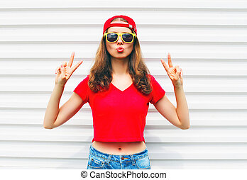 Fashion pretty cool woman in sunglasses and red t-shirt over white background
