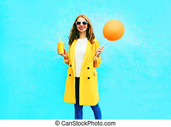 Fashion pretty smiling woman with orange air balloon holds cup of fruit juice on blue background