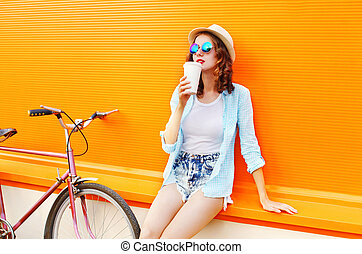 Fashion pretty woman drinks coffee from cup with bicycle over colorful orange background