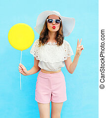 Fashion pretty woman in straw hat with air balloon over blue...